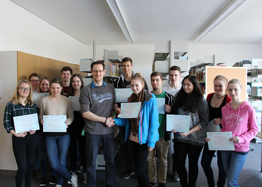 Herr Kern, der Leiter des DELF-Vorbereitungskurses, überreicht den stolzen Teilnehmern ihre Sprachdiplome.